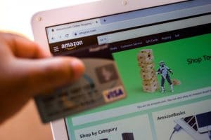 The Amazon.com website is shown on a laptop in the background and a person holds a bank card