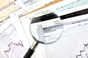 Amazon stock exchange ticker under magnifying glass on candlestick background