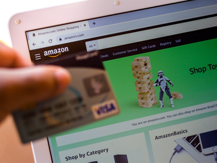 The Amazon.com website is shown on a laptop in the background and a person holds a bank card.